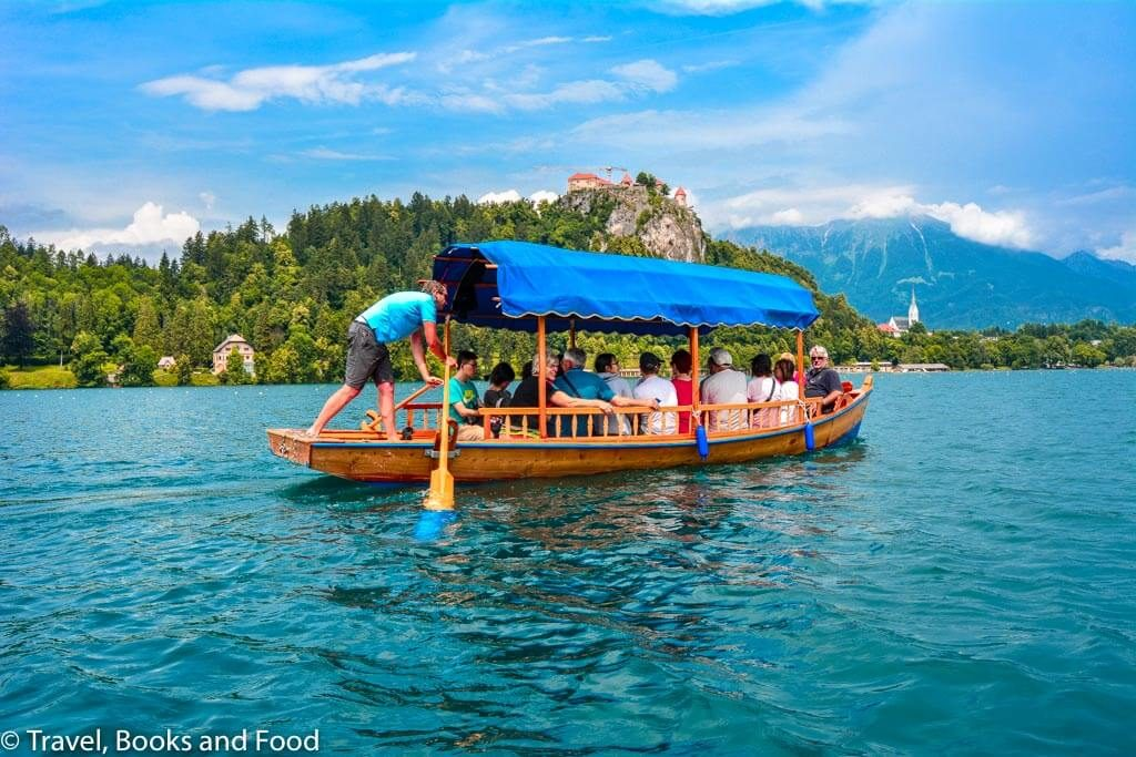 A gondola with lots of passengers in the middle of Lake amidst the Julian alps and the castle in the background
