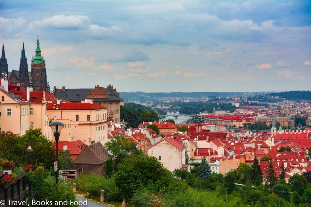 The city of Prague from one of the views of the city with the orange roofs and the Prague castle in the distance