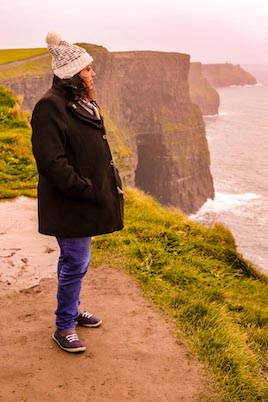 A photo of Soumya Nambiar, a well known Indian travel blogger staring into the distance at the Cliffs of Moher in Ireland