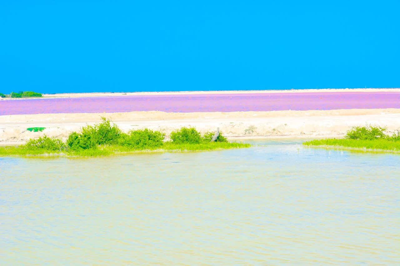 Start Here - A colorful photo with blue sky, white sand, green and pink waters from Mexico