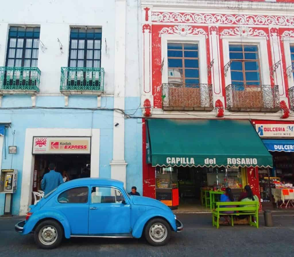 A blue Volkswagon Beetle parked in front of some colorful shops with Baroque architecture in Puebla