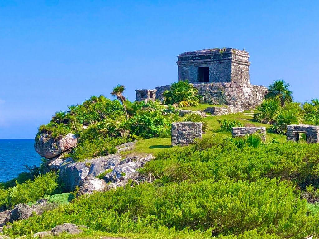 Tulum - Best places to visit in Mexico. A ruin on top of a hill in Tulum overlooking the sea on a sunny day