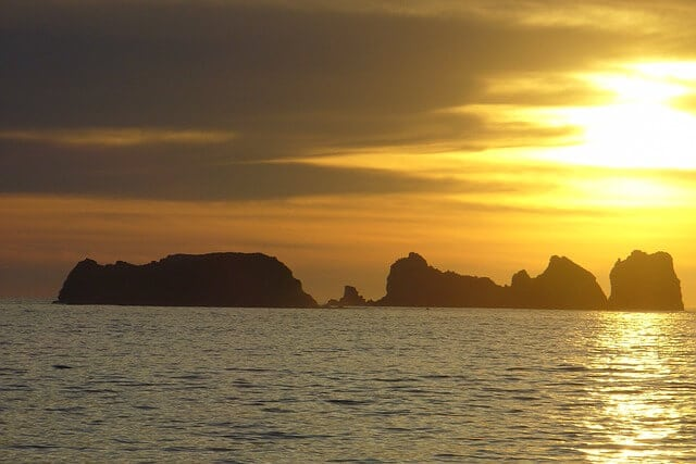 Some islands in the distance under an orange sunset