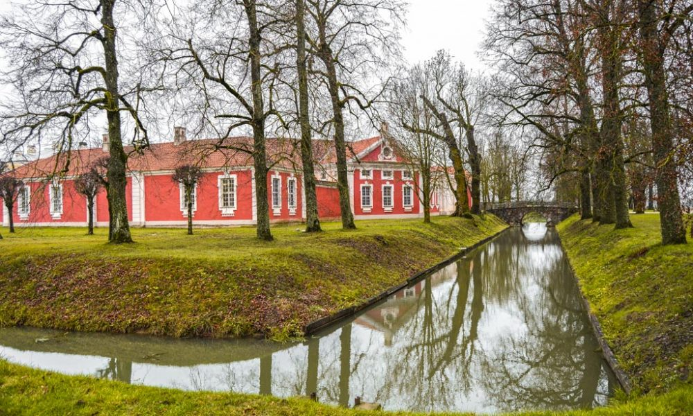A gorgeous house in Riga, Latvia surrounded by trees with a stream in front