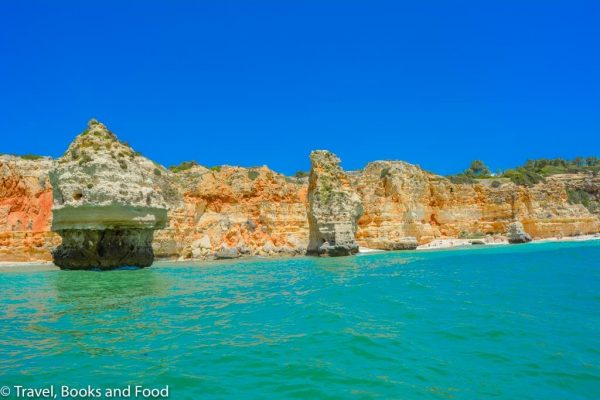 Turquoise waters against limestone cliffs in Algarve, one of my favorite European beach destinations
