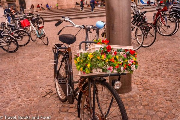 A cycle in a street with a colourful flower basket in Amsterdam, a must for your European vacation