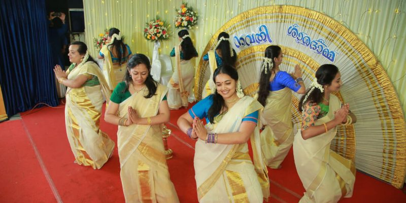 Women dancing in traditional Kerala attire