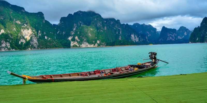A boar across some gorgeous mountains and a green lake