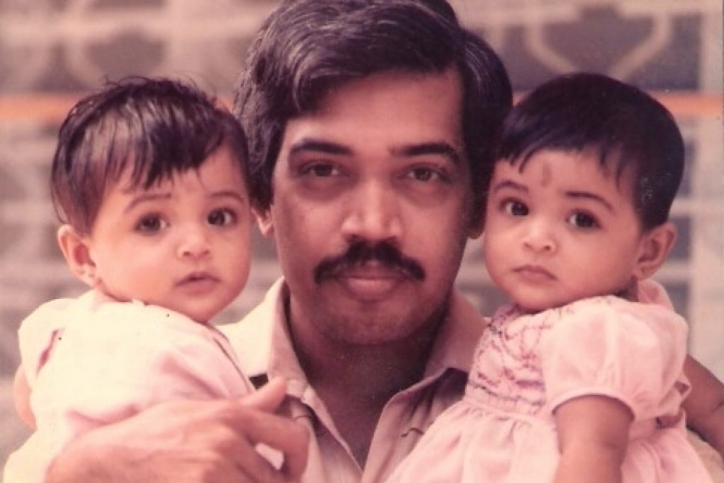 Dad carrying his twins on each arm